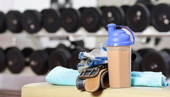Gym picture with weights and nutritonal shake.