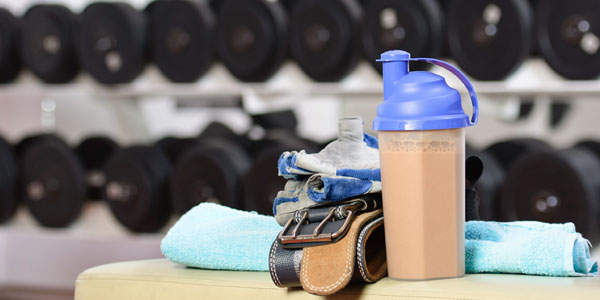 Protien shake, excercize equipment and dumbells in the background.